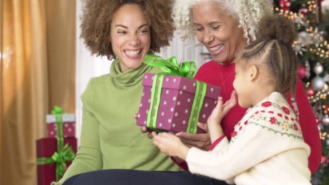 girl giving grandmother a christmas present - großmutter stock-videos und b-roll-filmmaterial