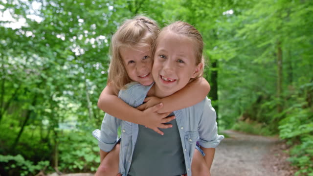 slo mo girl giving her little sister a piggyback ride up a forest path and smiling - sibling stock videos & royalty-free footage