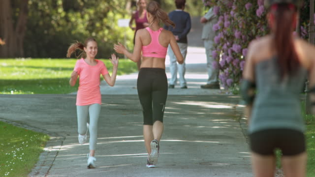 SLO MO Girl giving her mother a high five as they pass each other while running in the park