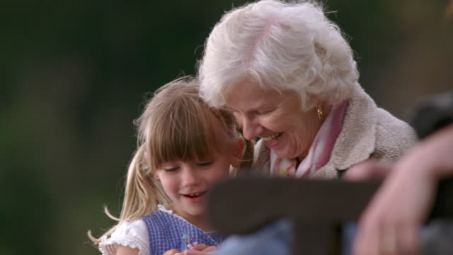 cu girl giving shell to her grandmother and hugging her in park / washington state, usa - animal shell stock videos & royalty-free footage