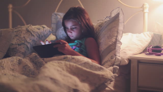 girl going to bed with electronic tablet - ora di andare a letto video stock e b–roll