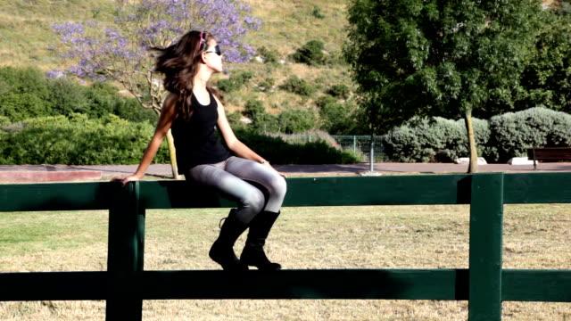 vídeos de stock e filmes b-roll de menina cumprimenta alguém sentado na vedação - vedação