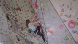 CLOSE UP: Girl grips on to a pinch hold while she loops her rope into carabiner.