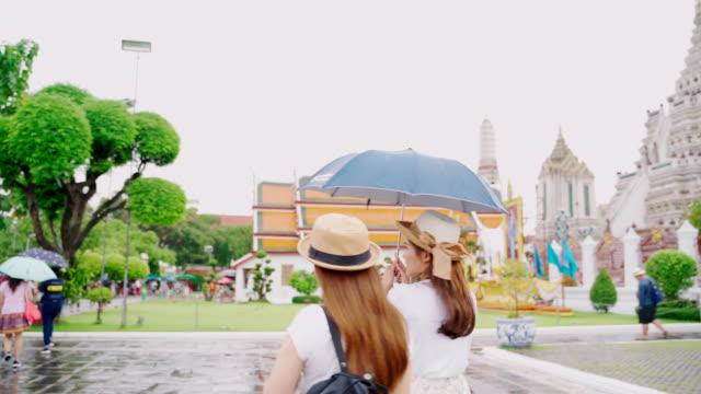 """stockvideo's en b-roll-footage met meisje gidsen van thailand's collega japans naar de belangrijkste attracties van het land te bezoeken. """" wat phra kaeo """"bezienswaardigheid van bangkok in thailand. - achterover leunen"""