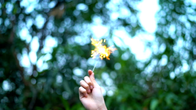 slo mo girl hand holding sparklers with nature tree background - sparkler stock videos & royalty-free footage