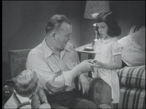 b/w 1951 girl handing pipe to father in armchair - 1951 stock videos & royalty-free footage
