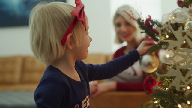 girl hanging ornament on christmas tree then high-fiving mother / vineyard, utah, united states - decorating the christmas tree stock videos & royalty-free footage