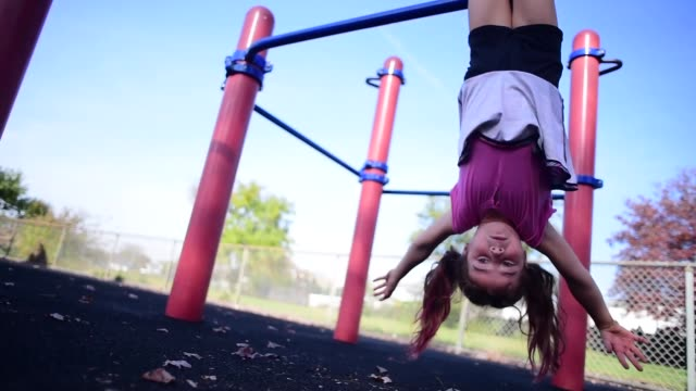 a girl hanging upside down on the monkey bars. - upside down stock videos & royalty-free footage
