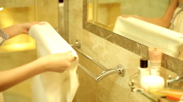 girl hangs a towel in the bathroom