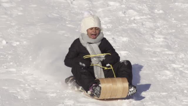 girl has fun sledding on a winter day - falla av bildbanksvideor och videomaterial från bakom kulisserna