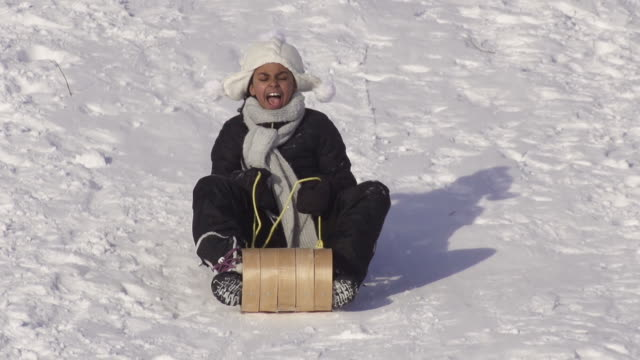 Girl has fun tobagganing on a winter day