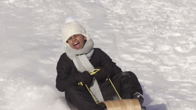 girl has fun tobagganing on a winter day - falla av bildbanksvideor och videomaterial från bakom kulisserna