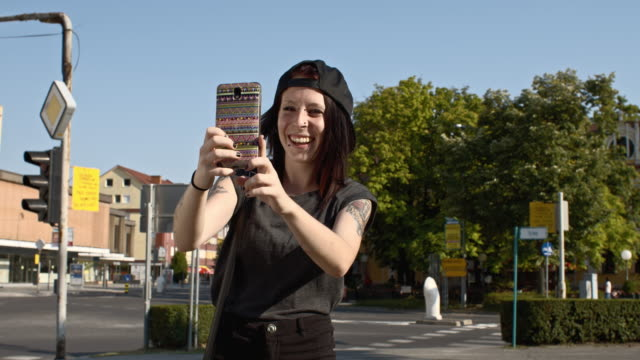 slo mo girl having a video call in the city - tattoo stock videos & royalty-free footage