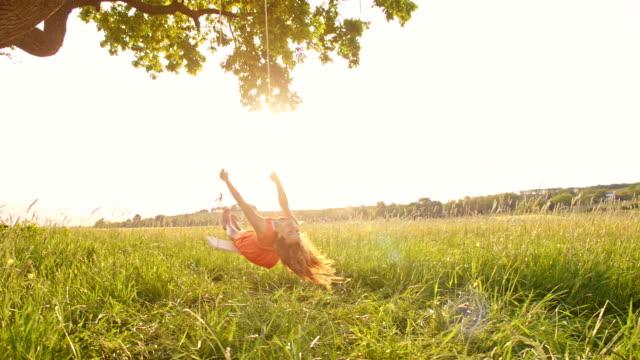 slo mo ガール楽しいスインギングに揺れる木 - ブランコ点の映像素材/bロール