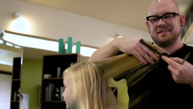 girl having her hair cut in a salon - sich verschönern stock-videos und b-roll-filmmaterial