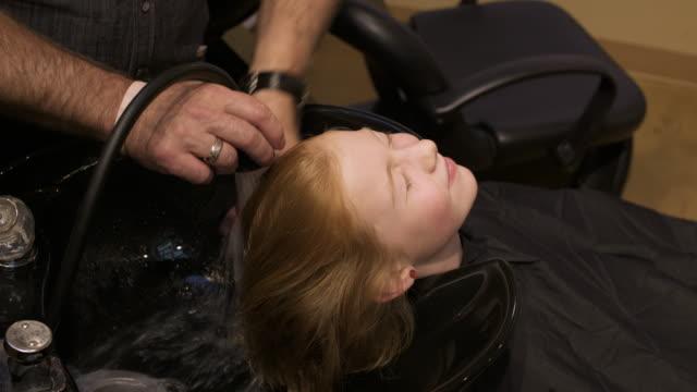 vídeos de stock, filmes e b-roll de girl having her hair washed by a hairdresser - cabelo de comprimento médio