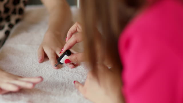 vidéos et rushes de girl having nails painted - manucure