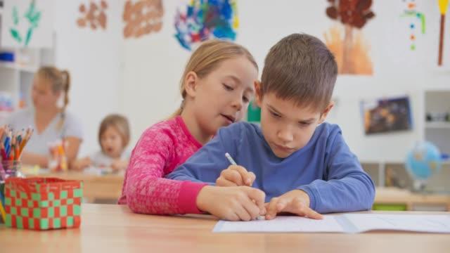 vidéos et rushes de ds fille aidant un garçon écrivant quelque chose dans son cahier dans la salle de classe brillante - gomme