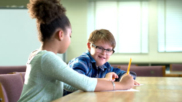 girl helping boy with down syndrome write in classroom - learning disability stock videos & royalty-free footage