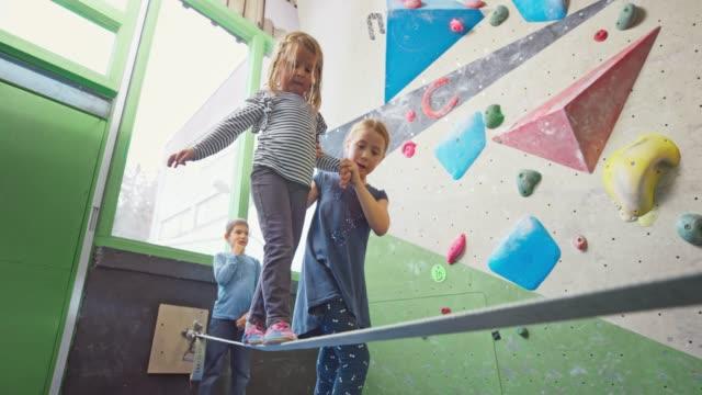 vídeos y material grabado en eventos de stock de chica ayudando a su hermana menor a caminar en el slackline en el gimnasio - equilibrio