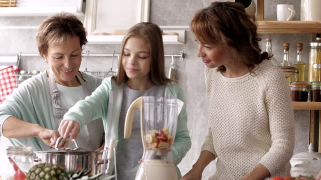 girl helping mother and grandmothers in the kitchen - abundance stock videos & royalty-free footage