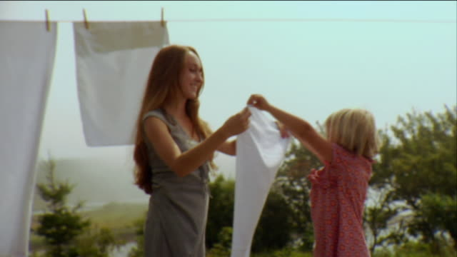 sm la ms td tu girl helping mother hang sheets on clothes line / vinalhaven, maine, usa - laundry stock videos & royalty-free footage