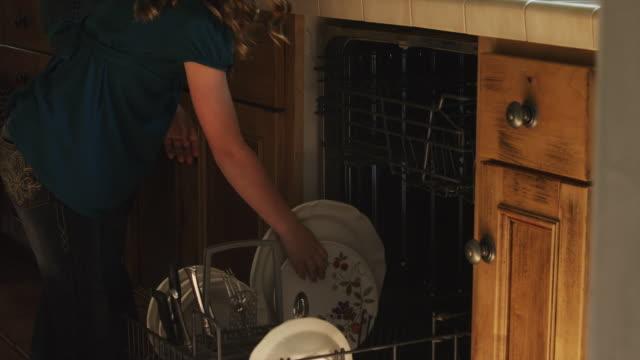 MS TU TD Girl (8-9) helping mother putting dishes into dishwasher / Cedar Hills, Utah, USA