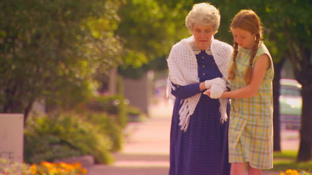 girl helping old woman across the street - mithilfe stock-videos und b-roll-filmmaterial