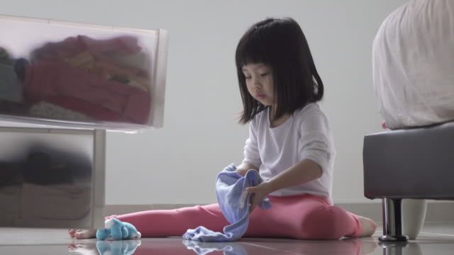 girl helping out with household chores. folding clothes and keeping it in chest of drawers. - chest of drawers stock videos & royalty-free footage