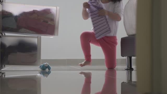 stockvideo's en b-roll-footage met meisje helpen met huishoudelijke klusjes. opvouwbare kleren en houd het in de commode. - wasmand