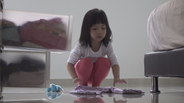 girl helping out with household chores. folding clothes and keeping it in chest of drawers. - nursery school child stock videos & royalty-free footage