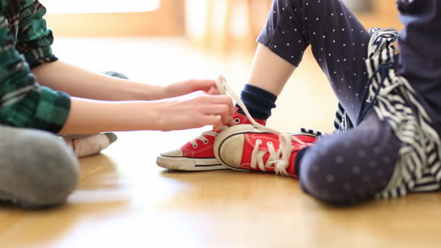 girl helping younger sister to tie shoelaces - shoelace stock videos and b-roll footage