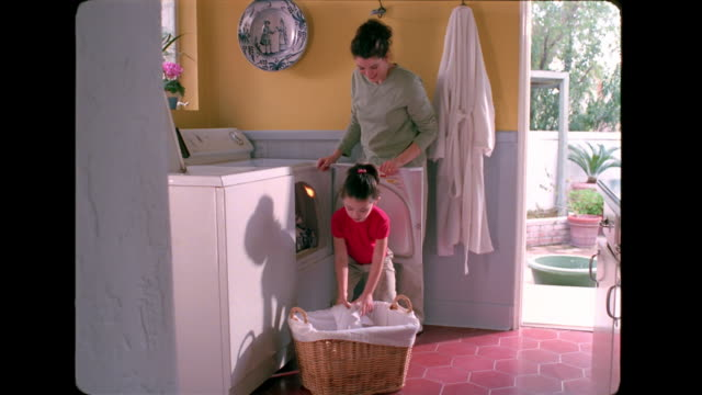 stockvideo's en b-roll-footage met a girl helps her mother place laundry in the dryer. - wasmand