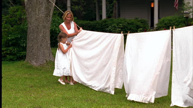a girl helps her mother stretch a sheet across a clothesline. - washing line stock videos & royalty-free footage