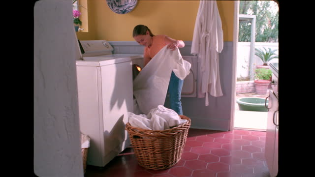 a girl helps her sister out of the laundry basket where she is hiding. - wäschekorb stock-videos und b-roll-filmmaterial