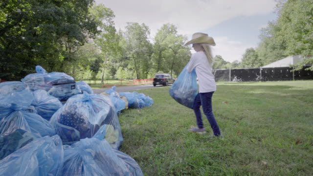 vídeos de stock e filmes b-roll de girl helps to clean up neighborhood park - lixo