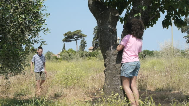 vidéos et rushes de girl hiding behind tree, boy finds and chases her - toscane