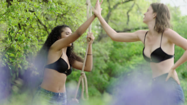 MS. Girl high fives friend and backs up with rope swing.