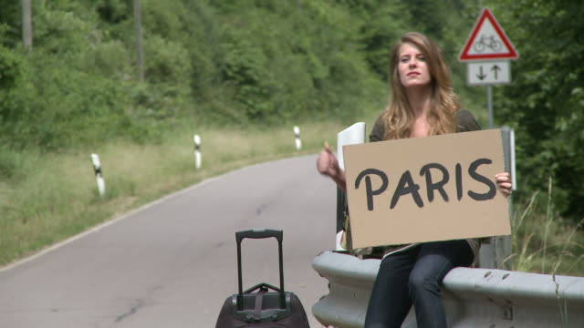 ms girl hitchhiker standing with sign / saarburg, rhineland-palatinate,  germany - ヒッチハイキング点の映像素材/bロール