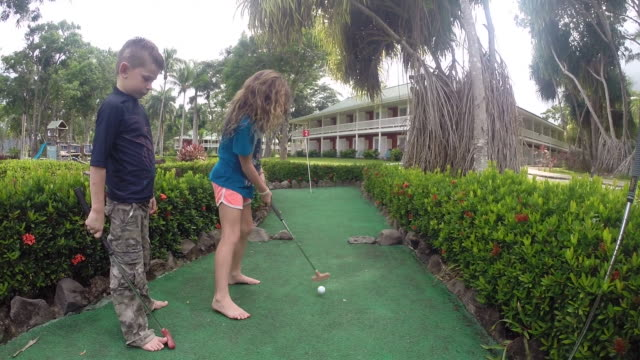 girl hits hole in one with brother standing beside her at mini golf course then high fives dad at resort. - kelly mason videos 個影片檔及 b 捲影像