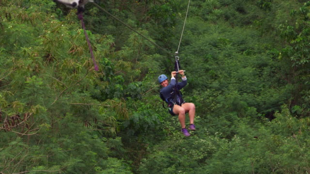 girl hits the platform at the end of a zipline - turtle bay hawaii stock videos and b-roll footage