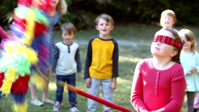Meisje slaan pinata, kinderen kijken op achtergrond