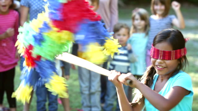 girl hitting pinata, children watching in background - mexican culture stock videos & royalty-free footage