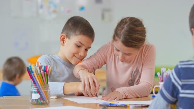 何かを描くのを助けるために少年の手を握っている少女 - 消しゴム点の映像素材/bロール