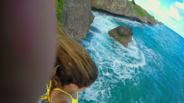 vídeos de stock e filmes b-roll de a girl holding a camera back at herself jumps off a high cliff into the ocean - só uma mulher jovem