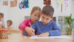 DS Girl holding a classmate's hand and helping him draw lines into his notebook
