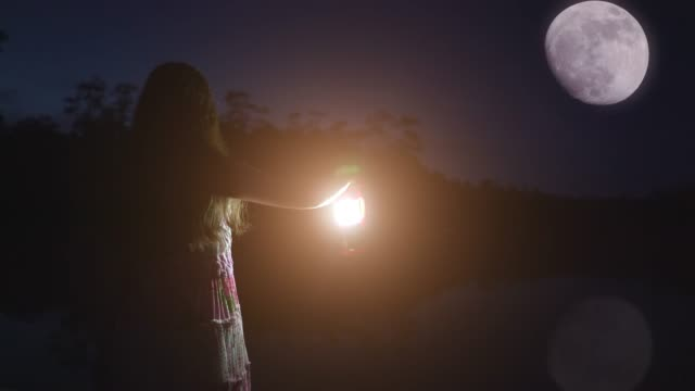 girl holding a lantern, looking at the moon. - atmosphere filter stock videos & royalty-free footage