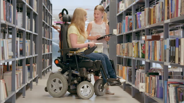 ds girl holding a tablet handing a book to a woman in the wheelchair - disability stock videos & royalty-free footage