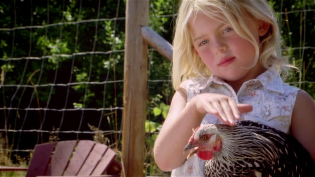 vidéos et rushes de girl holding and petting chicken / looking at camera and smiling - mignon