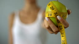 Girl holding apple wrapped in measuring tape, calculation of calories, diet